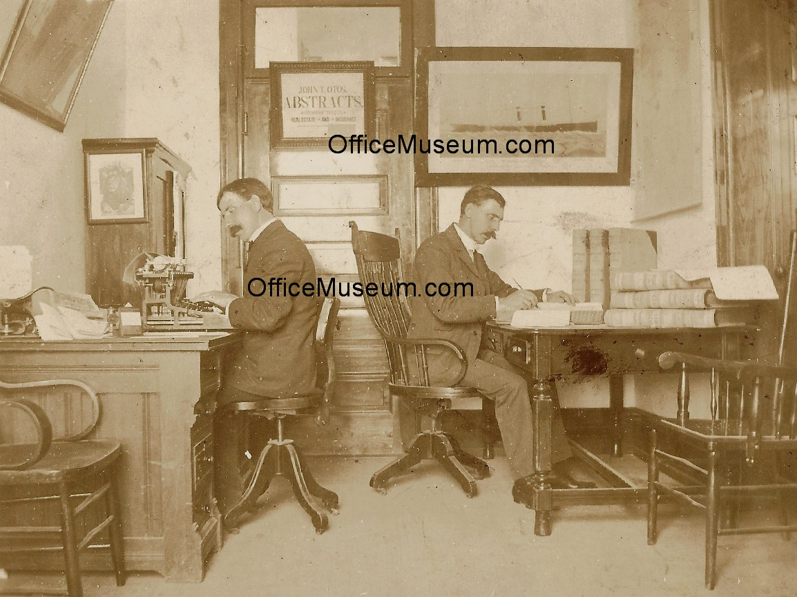 Two_men_in_office_with_upstrike_typewriter_plantation_desk_OM.jpg